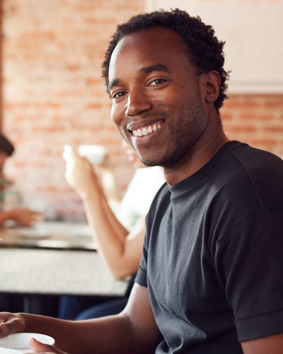 portrait-of-smiling-man-sitting-at-table-in-coffee-X7YY6PU.jpg